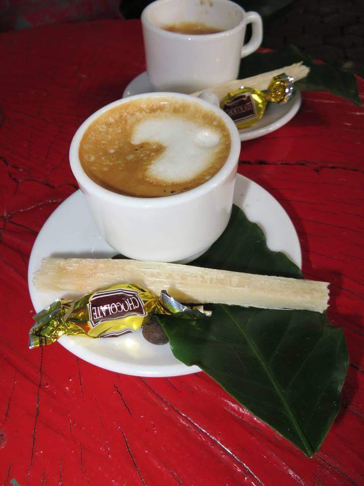 kava servirovana na bananovom liste, s palickou z cukrovej trstiny a kavovym zrnom v čkolade
